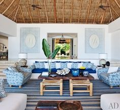 At a Mexican beach house by Martyn Lawrence Bullard, the living room sofa, with seat and back cushions of Chameleon fabric by Perennials, is flanked by custom-made chairs upholstered in Kaba Kaba linen by Bullard. Niches in the rear wall display Bali-inspired stenciling by artist Kelly Holden   archdigest.com