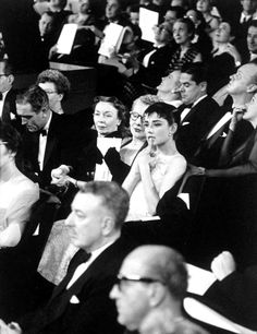 Audrey Hepburn in the audience for the 1954 Academy Awards ceremony at the NBC Century Theater in New York (the simultaneous West Coast ceremony was held at the RKO Pantages Theater in Hollywood)....