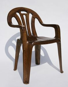 'Plastic Chair In Wood' reproduces the iconic plastic lawn chair in hand-carved elm. References the contrast between disposable, mass-produced goods and treasured, handcrafted objects.