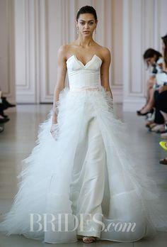 A chic @oscarprgirl wedding dress with a feathered overskirt | Brides.com