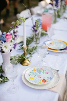 I wonder how difficult it is to get plates like these? They've done my exact idea with the gold, white candles and different vases of wildflowers.