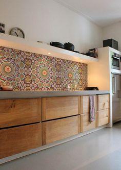 La crédence de cette cuisine est composée d'un papier-peint en vinyle lessivable au motif de mosaïque coloré et géométrique.