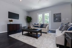 Living Room has a Juliet balcony and lots of wall space, grey paint and dark wood floors