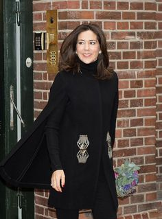 Crown Princess Mary of Denmark wore a stylish collarless black coat with silver embellishment and threw a cape on over the top.  She kept her makeup natural with just a slick of pink lipstick and blusher, adding a pair of diamond studs.