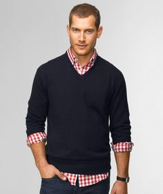 Casual preppy. V-neck sweater with pushed up sleeves, untucked shirt, dark denim jeans.