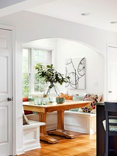 white kitchen banquette with abstract art, built in benches breakfast area