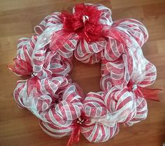 Simple elegance! Red and white stripe deco mesh wreath with red ribbon accents with some festive bells.