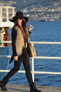 Love the different layers and mixed styles of this nude & black 'street style' outfit:wrap cardigan with longer-at-sides hem over a sheer blouse + black skinnies + furry vest + biker booties + handbag + floppy hat + round frame sunnies.Boho chic with an edgy rocker touch!