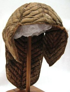 """Helmet liner dating 1600s, rounded slightly conical hill sewn by four triangular pieces. On the inside of the hill in the middle sewn a round flat """"bud"""". Kind / earflaps with slightly pointy bottom. Long neck display the same design. Herringbone patterned quilting. Outer shell of a heavy greyish linnelärft. Filling of wadding (wool or linen?). Inner lining of your rostbrut silk fabric in plain weave. Edging approximately 5 mm wide."""