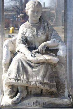 """Lulu E. Fellows - Died Nov. 23, 1883 Aged 16 Years. Inscription reads: """"Many hopes lie buried here."""" Lulu sits eternally beneath this tree, a wistful expression on her face. An open book is in her lap. The likeness in marble is badly worn, particularly the hands and nose. Years after this statue was placed over the grave, a protective glass box was erected."""