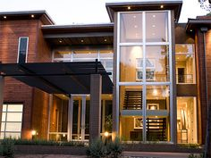Mid-century modern inspired home in Dallas, Texas, From left to right  - glass garage door front entry and porte cochere and stairwell.  , Home Exterior Design