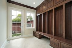 Side entrance mudroom with enormous dark wood bench and storage. Beige tile compliments cream walls and white trim.