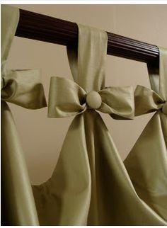 In this pretty and simple idea for tab top curtains, replace the bow with a pinecone from your yard glued into a pretty, sparkly ribbon to create a special custom header for your window treatments ~