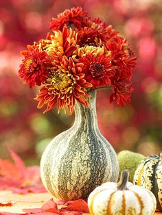 Cool idea ~ a gourd vase with mums.
