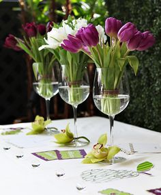 bunches of tulips displayed in oversize wine glasses