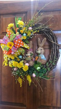 Get in the mood for spring with a grapevine wreath which features different type of yellow flowers enhanced by a multi-colored bow and surrounded with different types of greenery and Easter eggs. The center features a sitting and standing Sisal bunnies each cradling their