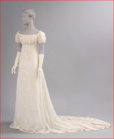 Sheer cotton plain weave dress with cotton embroidery in satin and cable stitches, possibly American, ca. 1800. The fine white fabric popular in the early 19th C., often imported from India, was frequently enhanced with whitework embroidery. In this example, contrastingly heavy cotton embroidery thread is used for the bands of floral sprigs and serpentine lines down the center front and around the train.