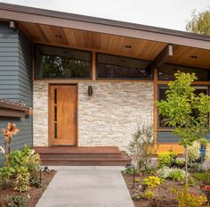 Beautiful entrance with wood door, stone surrounding, glass above, and siding for the rest