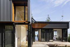 Bien qu'inspirée pour la fondation d'un hangar ou d'un abri de jardin, cette maison est bien plus qu'une de ces simples constructions. Sa structure mêle tôle ondulée, bois et façades en verre offrant  un certain charme industriel à l'ensemble.  Cette maison se trouve en bord d'océan, sur la côté Sud de la Nouvelle-Zélande. Loin d'une conception traditionnelle, ce cabanon amélioré et modernisé a été agencé de manière à offrir un petit patio en son sein et de magnifiques vues sur l'océan.