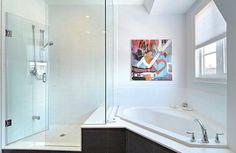 petite baignoire d angle, une cabine de douche et une peinture abstraite