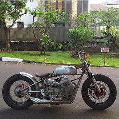 Moto Guzzi hardtail custom with small gas tank and headlight, bare metal body work and frame and black rims