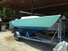 An Ensign sailboat with fresh topside paint.