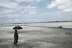 BANGLADESH. Kurigram District. 2010. A man uses an umbrella against the harsh midday sun, on a typical lowlying 'char', or silt island in the middle of the Brahmaputra river.