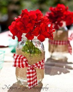 Burlap and gingham wrapped around Mason jars filled with red geraniums. Always a hit!