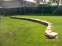 This low retaining wall adds more interest to this yard with a slightly sloped backyard. Adding garden beds in and around the wall will soften it up with colour. Picture compliments of Dream-yard.