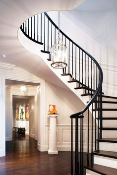 A round entry hall leads to a three-story central circular stairway that winds up to a round skylight at the top, from which hang English lanterns.