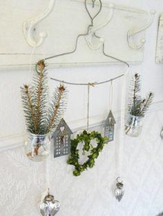 Pendeloques accrochées à un joli cintre, pots de verre suspendus garnis de branches de pin.