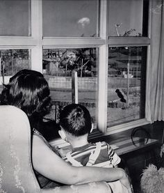 """Safe in the living room of her Las Vegas, Nevada, home, Mrs. Jacqueline Buck and her son watch the mushrooming cloud from an atomic test blast some 75 miles away,"" April 21, 1953"
