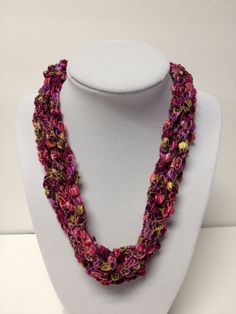 "Check my blog: centraltexascrafter.com or direct link below. Want the look of beads but enjoy the light-weight feel of yarn?  Handcrafted, gorgeous rosy colors of pink, purple with green necklace. Length can be adjusted from 18"" to 24"" with ease. No metal, no clasps - easy to put on and wear. You'll get so many comments on your ""beads"" - this unique necklace will garner you many compliments!"