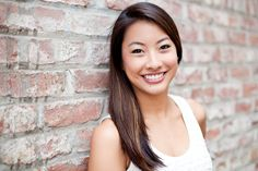 Brick headshot, I like the textured background, The white in the bricks really complements her top. Her hair is styled great and nice smile.