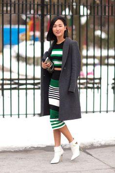 Nicole Warne inspiração street style de look listrado com sobretudo cinza, top cropped listrado preto, branco e verde, saia lápis listrada preta, branca e verde, ankle boots brancas, bolsa preta.