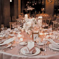 Tables were topped with champagne linens, candles, and centerpieces of roses, orchids, ranunculuses, and branches