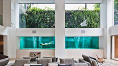 Swimmers in a pool at this renovated residence in São Paulo can be watched from the living room through thick glass panels, like fish in an aquarium tank.