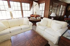 Contrast dark wood paneling with comfy white furniture.
