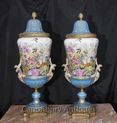 - Available to view in the Canonbury Antiques Hertfordshire showroom, just 25 minutes north of London<BR>  - Gorgeous French Sevres style porcelain vases or urns<BR> - Very vivid tropical floral panels complete with a hovering humming bird<BR> - Definitely ready to add light and vivid energy to any room<BR> - Love the shade of cyan blue offset by gold ormolu fixtures<BR> - Ormolu is original and has a great patina<BR> - Purchased from a dealer on Marche Dauphine at the Paris Les Puces…