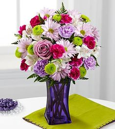 The FTD Purple Pop Bouquet comes straight from our fun, trendy and simply irresistible Color Confection Collection. Perfectly grape, this stunning flower bouquet consists of lavender roses, carnations and traditional daisies offset by fuchsia mini carnations, green button poms and white Peruvian lilies to create an arrangement popping with color and style. Presented in a violet purple glass vase to give it a posh purple pop.