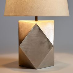 Crafted of faceted metal with a pewter finish, our exclusive table lamp adds a geometric element to any room. Subtle brushwork details add a delicate texture to its organic appearance.