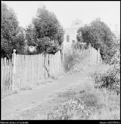 Stacey, Wes (Wesley), 1941- View along a fence to the hospital, Maldon, Victoria, ca. 1970 [picture]
