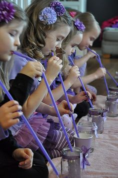 kids party game: The Straw Game=The girls had a full purple cup and an empty glass jar. They had to use their long straw to move the water from one cup to the other.