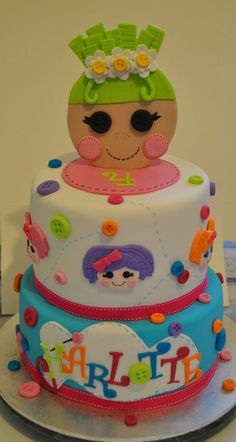 Lalaloopsy cake for my daughter! Vanilla spot cake inside with white choc ganache. Pix E flutters topper, and Pillow Featherbed, Bea Spells Alot, Blossom Flowerpot, Mittens Fluff n Stuff and Jewel Sparkles around the top tier :)