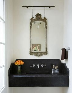 Simple, yet elegant powder room by designer Jim Howard. The black stone wall mounted wall sink and faucets are tucked back into the contrasting crisp white walls.