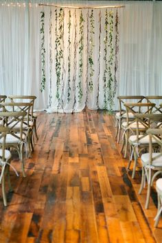 Create the look of a woodsy, ethereal wedding indoors with this floral backdrop. Create a beautiful contrast and perk up a plain white curtain with crisp, green leaves. The best part? It's easy to make yourself, and fits right in with a minimalist theme.     Get the tutorial at  Free People .