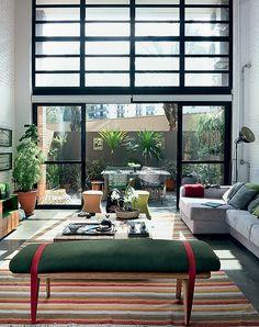 A sala do apartamento tem jeito de casa fresca, graças ao acesso ao terraço e o pé-direito duplo com janelas. Muitas plantas completam o visual. Projeto da arquiteta Bruna Riscali