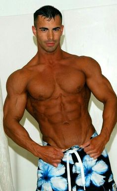 Tall, dark, muscled, and handsome in blue flowered swim trunks.
