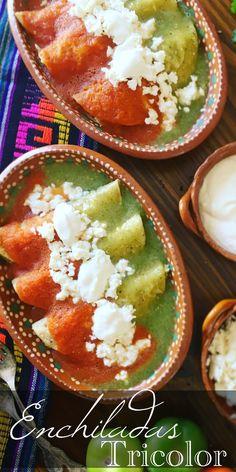 Tortillas de maíz rellenas de pechuga de pollo cocida y deshebrada, bañadas por la mitad con salsa verde y salsa roja, y espolvoreadas con queso fresco y un toquecito de crema.