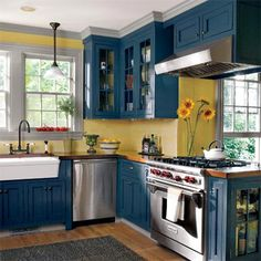 Kitchen ~ teal ~ Under the care of an anxious new owner, Paul Rogers, an old whaling cottage circa 1840s was saved and restored. In the pretty blue and yellow kitchen, ceiling-hung cabinets hold the vent hood and frame an opening that allows the cook to keep an eye on guests. The white apron-front sink, seeded-glass cabinet doors, Victorian-style faucet, and butcher-block counters all add a cottage accents.